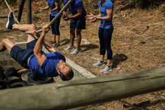 Man crossing the rope during obstacle course while people cheering him Royalty Free Stock Images