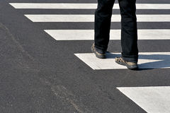 Man crossing street. Legs of man in black jeans and sneakers crossing street Royalty Free Stock Image