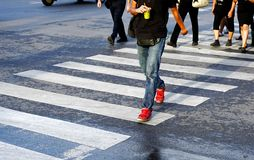 Man crossing the street crosswalk with crowd of people during rush hour, Bangkok Thailand. Royalty Free Stock Photos