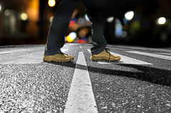 Man crossing street at night. Feet of man crossing street late at night Royalty Free Stock Photo