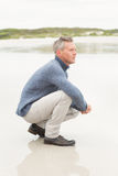 Man crouched down at the shore Royalty Free Stock Images