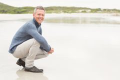 Man crouched down at the shore Royalty Free Stock Photography