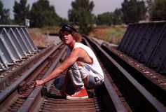 Man crouching. By railway tracks royalty free stock photo