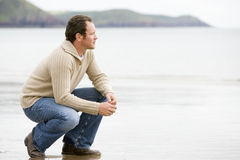 Man crouching on beach Royalty Free Stock Photo