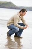 Man crouching on beach. Smiling Stock Images
