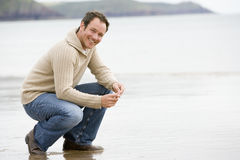 Man crouching on beach. Smiling Royalty Free Stock Photo