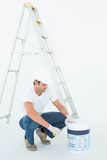Man crouching while opening paint pot. Full length of man crouching while opening paint pot over white background Stock Images