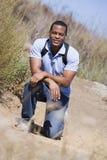 Man crouching on path to beach smiling Stock Photo