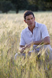 Man crouching in rural field Stock Photo