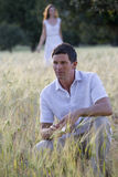 Man crouching in rural field Royalty Free Stock Image