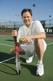 Man crouching on Tennis Court holding tennis racket and ball portrait Royalty Free Stock Photo