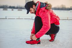 Man tying a left sneaker on a snowy ground. Man crouching while  tying a left sneaker on a snowy ground Royalty Free Stock Photos
