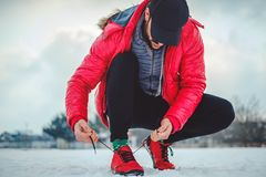 Man tying a right sneaker on a snowy ground. Man crouching while  tying a right sneaker on a snowy ground Royalty Free Stock Photos