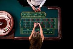 Man croupier och kvinnan som spelar rouletten på tabellen i kasinot Bästa sikt på en grön tabell för roulett med ett band Arkivbild