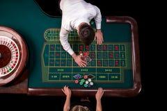 Man croupier och kvinnan som spelar rouletten på tabellen i kasinot Bästa sikt på en grön tabell för roulett med ett band Royaltyfri Bild