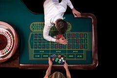 Man croupier och kvinnan som spelar rouletten på tabellen i kasinot Bästa sikt på en grön tabell för roulett med ett band Royaltyfria Foton