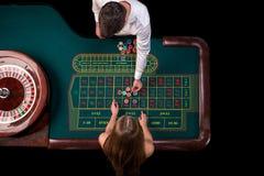 Man croupier och kvinnan som spelar rouletten på tabellen i kasinot Bästa sikt på en grön tabell för roulett med ett band Fotografering för Bildbyråer