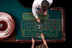 Man croupier och kvinnan som spelar rouletten på tabellen i kasinot Bästa sikt på en grön tabell för roulett med ett band arkivfoton