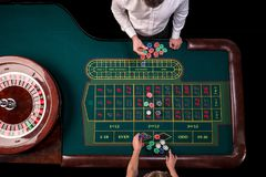 Man croupier and woman playing roulette at the table in the casino. Top view at a roulette green table with a tape. Man croupier and women playing roulette at stock images