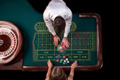 Man croupier and woman playing roulette at the table in the casino. Top view at a roulette green table with a tape. Man croupier and women playing roulette at royalty free stock images