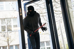 Man With Crowbar Entering Into House. Hooded man with crowbar entering into house Royalty Free Stock Photo