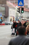 Man in the crowd. Image of a young businessman crossing a street in a city.Selective focus on the man with blur on the others people Royalty Free Stock Image