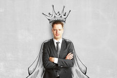 Man with crown and cape. Handsome young european man with drawn crown and cape on concrete wall background. Leadership concept stock images