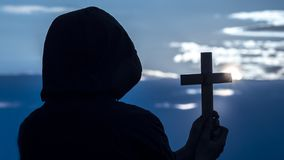 A man with a crucifix in his hands looks at the moon in the sky royalty free stock image