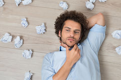 Man With Crumpled Papers Lying On Floor. Contemplated Young Man Lying On Floor Surrounded With Crumpled Paper royalty free stock photos