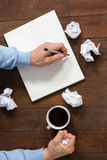 Man crumpling paper while writing on notepad Royalty Free Stock Photography
