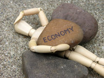 Man crushed by the economy. A mannequin crushed by rocks representing the economy Royalty Free Stock Photo