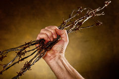 Man crushes barbed wire Royalty Free Stock Images