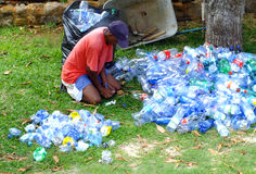 Man crushing plastic bottles. Man sitting down in front of pile of plastic bottles and crushes them individually in order to make them ready for recycling Royalty Free Stock Images
