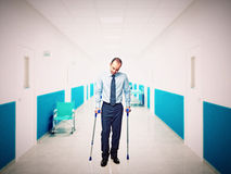 Man with crutch in hospital Stock Images