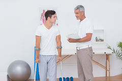 Man with crutch speaking with his doctor Stock Photography