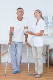 Man with crutch speaking with his doctor Royalty Free Stock Photography
