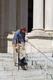 Man On Crutches. And wearing an ankle cast makes his way down concrete steps in front of a county courthouse Stock Images