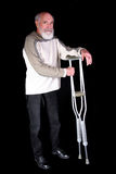 Man with crutches. Senior married man holding crutches isolated on black background Stock Photos