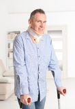 Man with crutches and crevical collar Royalty Free Stock Image