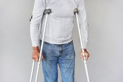Man with crutch. Close-up. Side view royalty free stock image