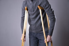 Man on crutches on a gray background. Studio shot Royalty Free Stock Photos