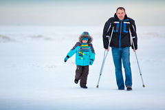 Man with crutches and his little son outdoors Royalty Free Stock Photos