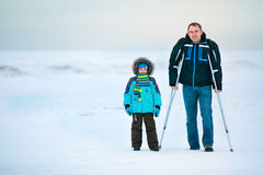 Man with crutches and his son walking outdoors. Man with crutches together with son walking along winter beach Royalty Free Stock Images