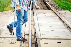 Man with crutches on railway crossing stock images