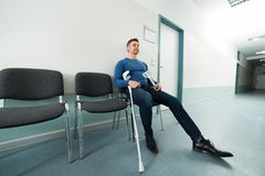Man with crutches sitting on chair Stock Image