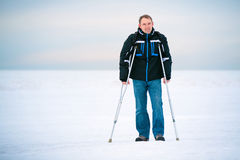 Man with crutches walking outdoors Stock Images