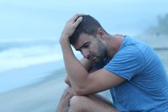 Man crying at the beach.  stock photography