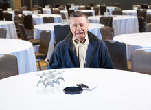 Man crying in empty conference room. Senior male weeping in empty meeting room workplace harassment Royalty Free Stock Image