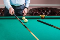 Man with cue opposite to Russian billiard table. Billiard player ponders blow Stock Images