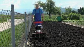 Man cultivating land in slow motion. Older man working on own farm land, preparing for planting bio vegetables stock footage